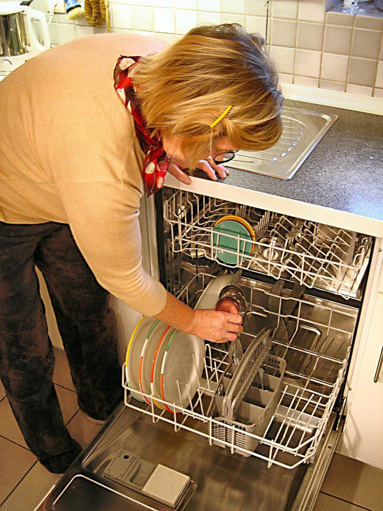 A woman leans over a dishwasher full of dishes.