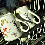 The top rack of a dishwasher with tea cups in it, which is why you need to know how to clean a dishwasher.